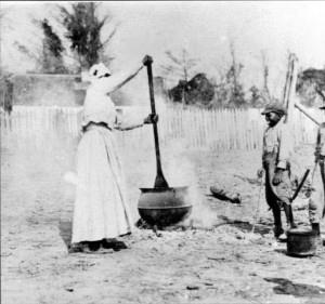 Black woman stirring kettle over open fire with large oar