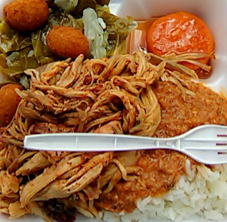 BBQ plate from McCabe's with stewed tomato, collards, hush puppies, hash and rice, and pulled pork with plastic fork on top.