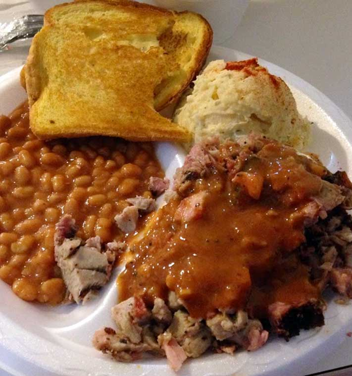 Chopped Barbecue Plate with beans, toast, and potato salad.