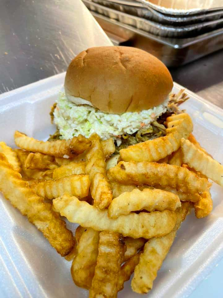 BBQ sandwich topped with slaw and fries in styrofoam tray.