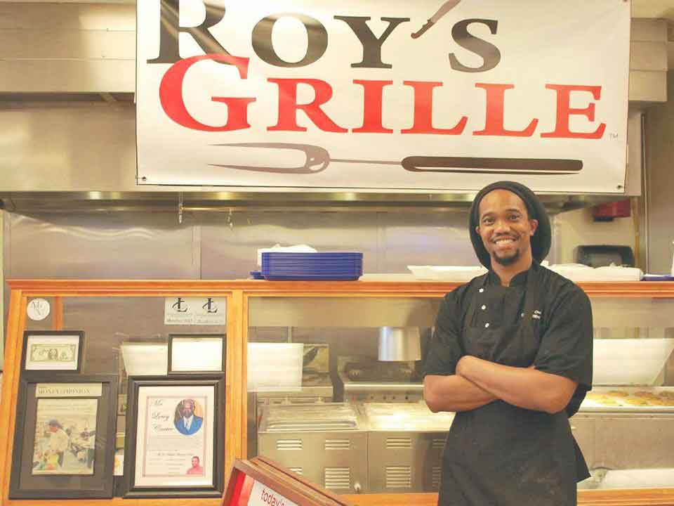 Chris Williams standing in front of his order station at Roy's Grille.