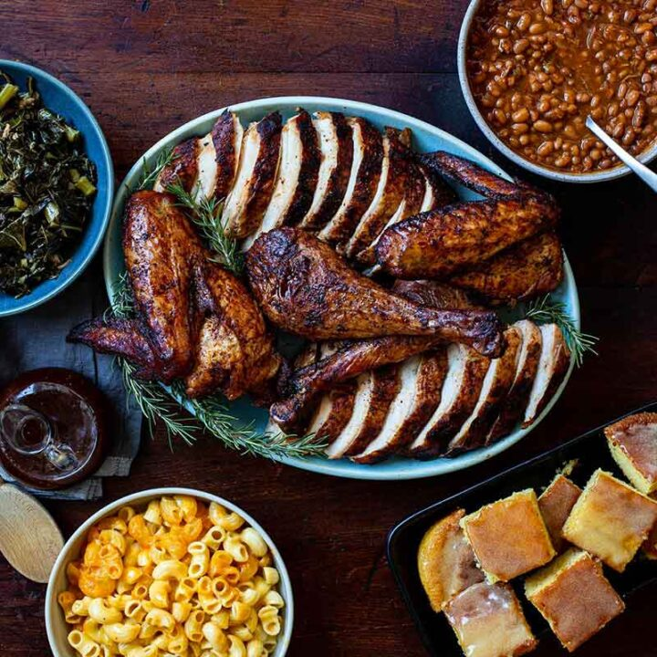 Rodney Scott's Smoked Turkey cut up on platter surrounded with various side dishes in bowls.