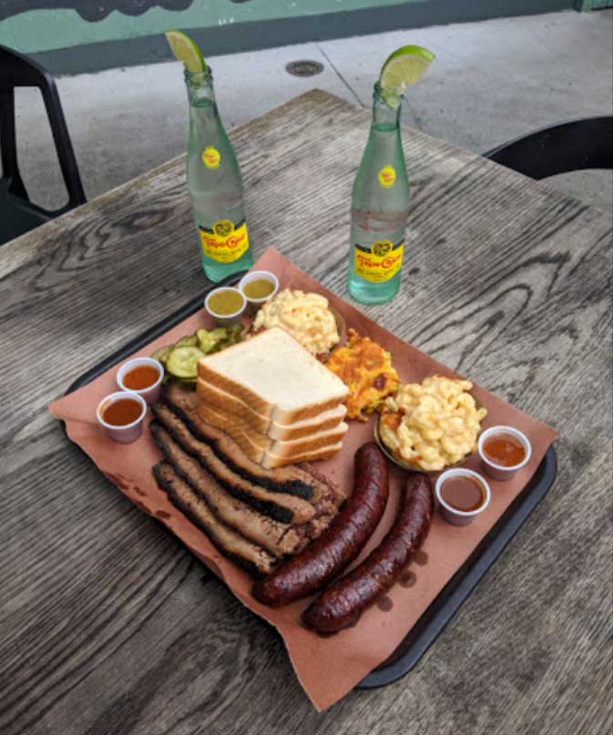 Brisket and Hot Guts Sausage with Mac n cheese, corn pudding, pickles and sauces.