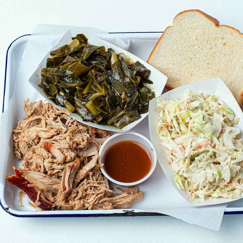 Pulled pork platter with collards, slaw, sauce, and white bread on metal tray with white butcher paper.
