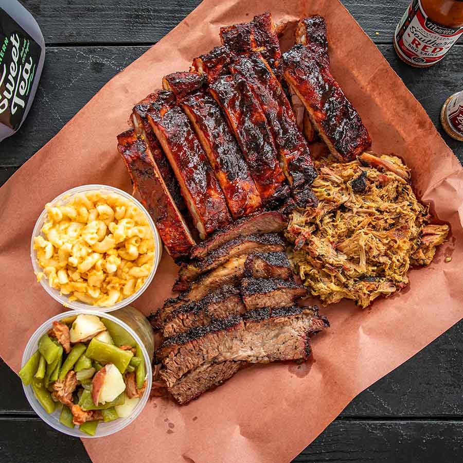 Ribs, pulled pork, and brisket on butcher paper with plastic containers of Mac and cheese and green beans from Melvin's Bar-B-Que.