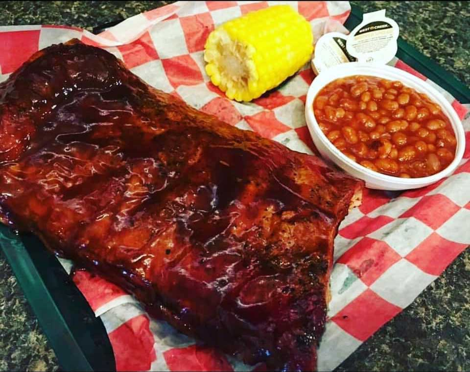 Glazed ribs with a side of corn on the cob and baked beans