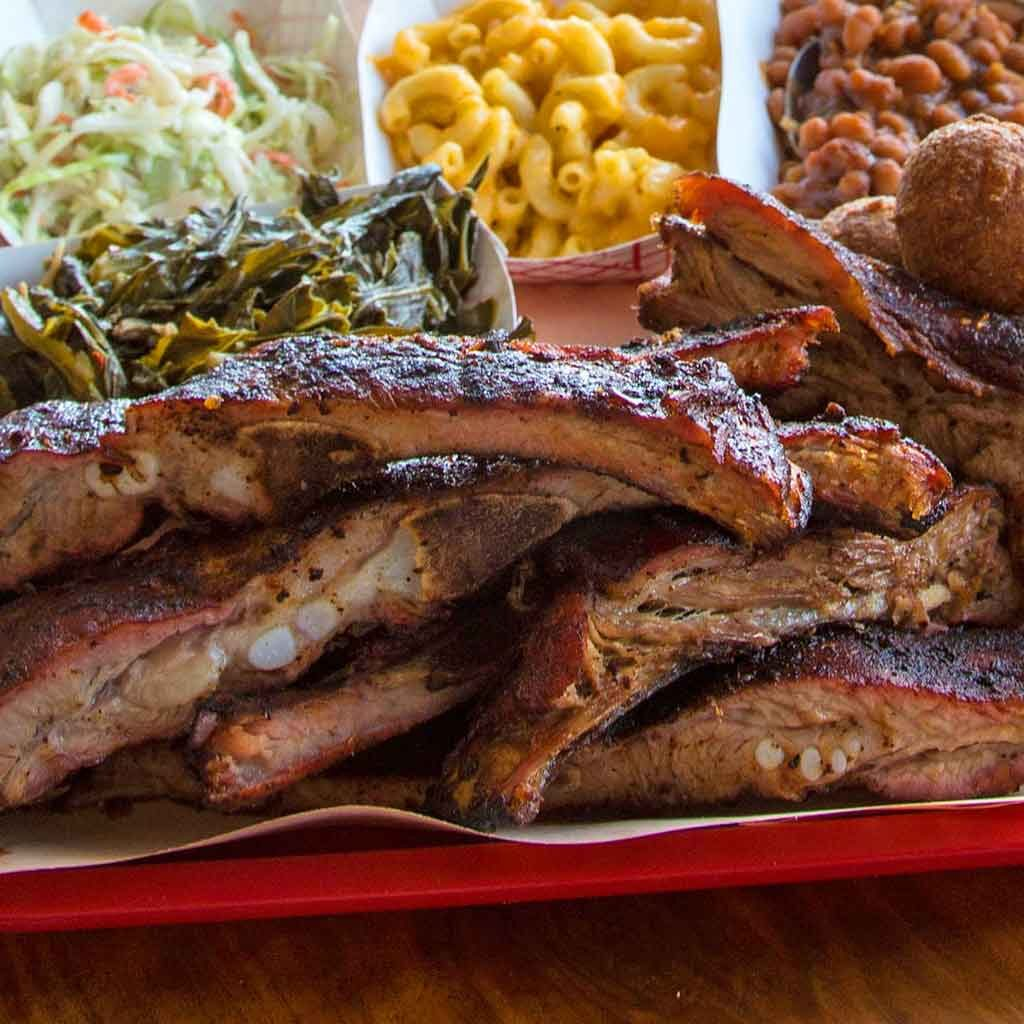 Ribs from Rodney Scott with several sides in the background.