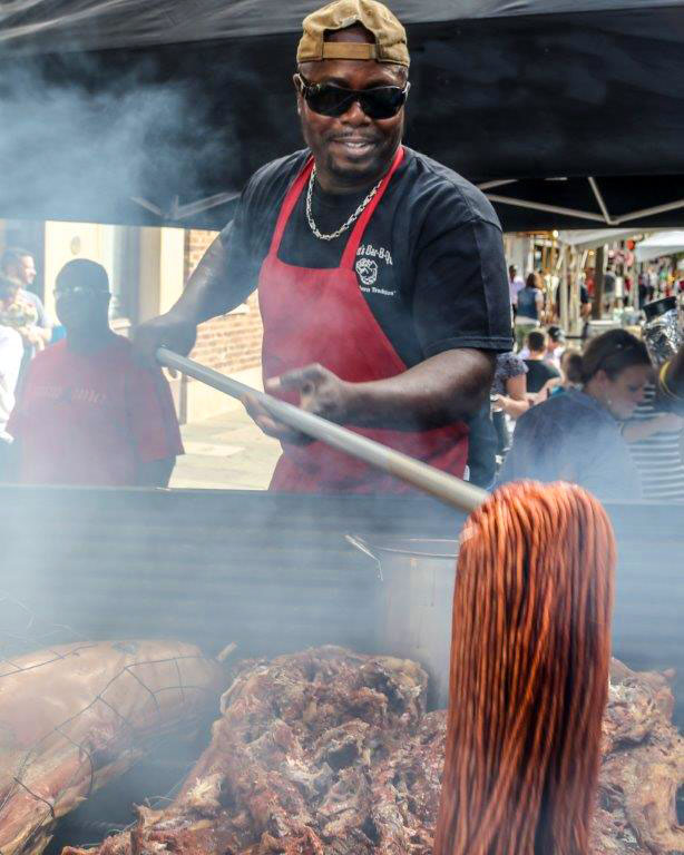 Rodney Scott mopping whole hogs on pit for barbecue
